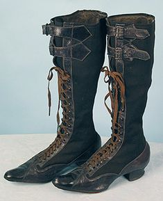 "Riding Boots, c1890; Black leather, black wool and brown cotton gabardine, metal eyelets, hooks and buckles, stacked wood heels, dark brown shoe laces. Provenance: Boots belonged to Mrs. Henry Ford. Label: Etched into sole of boot, partly legible.  L, 10""; Wd, 2.5""; Heel Ht, 1""; Boot Ht 15"".  By the end of the 19th century, the most popular physical activities for a lady were horse back riding, bicycling and tennis. The soles are scored in horizontal bands which allowed better foot purchase."