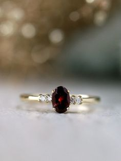 Never underestimate the power small pieces can hold. Our petite ring may seem delicate but it packs quite the punch with its exquisite framework. The dashing garnet is cut into an oval shape that enamours the eye in its brilliance while the baby diamonds Garnet Jewelry, Garnet Rings, Gold Diamond Rings, Gemstone Rings, Ruby Rings, Garnet Birthstone Rings, Pink Rings, Garnet And Diamond Ring, Oval Diamond