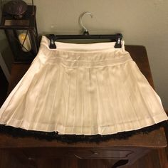 Cream bebe pleated skirt, with black lace underlay Pleated silk skirt with a lining underneath so that your undergarments wont show through, very light fabric.  Has a black lace trim on the lining (see photo).  Dry clean only.  Zipper back. 96% silk, 4% spandex.  Never worn, I love skirts but the weather is too cold for me here! bebe Skirts Mini