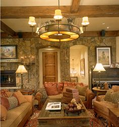 Rustic living area, with a rock wall and terrific light fixture
