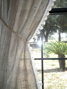 burlap curtains, crochet trim(or maybe lace would be cute?), tied with twine. Love!