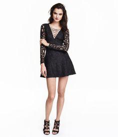 Kurzes, leicht ausgestelltes Kleid aus Spitze. Das Kleid hat einen V-Ausschnitt mit dekorativer Schnürung vorn und im Rücken einen verdeckten Reißverschluss. Lange Ärmel aus durchbrochener Spitze. Jerseyfutter.