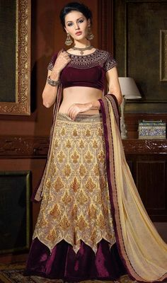 Add a touch of elegance to your look with this beige and violet color embroidered net lehenga choli. The attractive lace, stones and resham work throughout the attire is awe-inspiring. #netlehengacholi #embroideredworklehengacholidesign #partywearlehengas