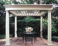 pergola with columns over outdoor table and chairs crown molding on pergola.  square lattice
