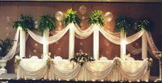DECORATION by Wedding Specialties, Orlando — This Wedding Backdrop will frame your wedding party photos using a combination of traditional Roman columns with lights, greens, balloon bubbles and elegant fabric drapery on columns and table front.