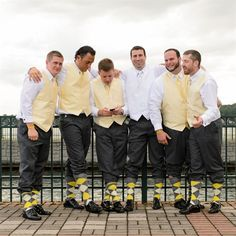 Playful Groomsmen With Matching Vests and Socks