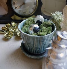 More old green McCoy pottery (a planter with attached saucer) filled with moss and mercury glass ornaments.