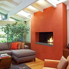 Bold Fireplace Color- Building up the facadeto make it thicker and covering it in vibrant tomato bisque-hued plaster turned the hearth into a showpiece. (Southern Living online)