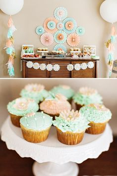 Beautiful Mint Gold Peach Dessert Table with flower cupcakes, paper rosette backdrop, and giant balloons with tissue tassels.