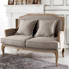 Pairing a distressed shabby chic frame and warm beige upholstery, this handsome settee brings pastoral elegance to your living room or parlor.