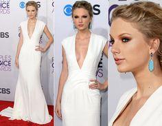 Taylor Swift ficou muito sexy com vestido branco de cauda e decote poderoso da grife Ralph Lauren. Minimalista, ela deixou todo foco para a parte de cima da produção, com os maxibrincos azul-água.