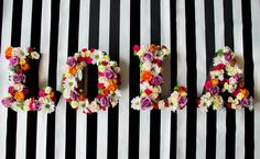 Floral hanging letters on black and white stripes. Baby shower flowers. Purple roses, hot pink roses, hot pink spray roses, orange ranunculus, yellow carnations, white daisies, blush spray roses, dusty miller. By Gold Leaf Floral // @goldleaffloral. Photo by Brittny Rene Photo @brittnyrenephoto