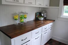 Super glossy butcher block counter top--restained Numerar Ikea butcher block. I really like the wainscoting as well.