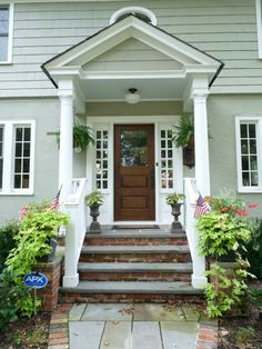 Dark wood front door with white trim.  Love the symmetrical plants on either side for balance.