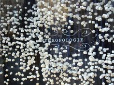 Anthropologie window displays visual merchandising  -  marshmallows strung on fishing line seem to be floating in the window  -  great for Halloween or snowy season