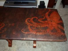 This is a close up of the larger octopus. This table was done in metallic foil. Refurbish, Metallic foils, paint, decorative painting, furniture, table, distressing, buttons, octopus, stain, table. dining room table, rehab.