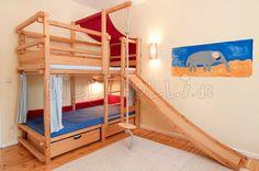 Etagenbett mit Rutsche, Kletterseil, Schaukelteller und Bettkästen, unten Vorhänge und Polsterkissen. Die Leiter ist hier in Position B, die Rutsche in Position A.