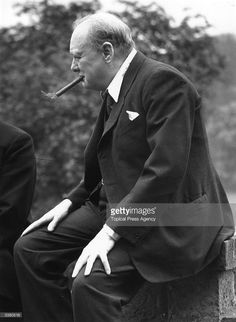 British politician Winston Churchill (1874 - 1965) smoking a cigar, at his home in Chartwell, Kent.