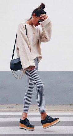 Trendy shoes with an oversized knit sweater and striped pants