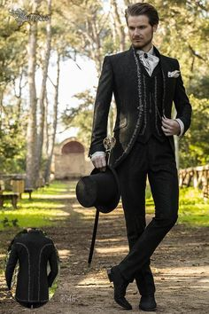 Baroque groom suit made of black jacquard fabric. This vintage costume is a mao collar frock coat with silver embroidery, chest pocket, tailoring pockets with stylish inclined flaps and a closing brooch. Wedding Men, Wedding Suits, Dream Wedding, Wedding Dress, Groom Suit Vintage, Wedding Suit Collection, Baroque, Groom And Groomsmen Attire, Groom Suits