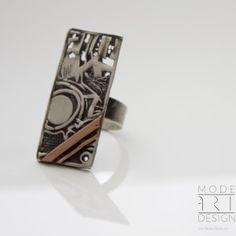Niezwykle piękny pierścionek autorstwa Doriana Grabowskiego. Wykonany ręcznie ze srebra próby 925 i miedzi, techniką galwanoplastyki. Wspaniale prezentuje się w zestawie z bransoletką i wisiorem. Idealna propozycja na wyjątkowy prezent.