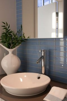 Awesome tile idea, and the color is Wedgewood blue. Not keen on the bowl and sink but think that the tile could still look good with a more Transitional flavor to hardware.