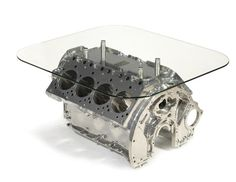 A Rolls-Royce 6.75 V8 engine cylinder block coffee table. Prior to the takeover by BMW in 1998 Rolls-Royce made use of the L Series V8, an engine that had been developed in the 1950s and still remains in use today – in modified form of course. This coffee table uses an L Series V8 as its base, before the table was built the engine block was stripped and subject to three stage chemical cleaning to remove all the old engine oil, junk and filth. It was then chromed and had four legs fitted.