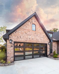 Brick House Exterior Discover Black glass garage door with light pink brick and herringbone accents Modern black glass garage door w/ light orange pink brick herringbone brick accents black exterior trim and black modern exterior lights Garage Door Styles, Garage Door Design, House Exterior Color Schemes, House Paint Exterior, Style At Home, Orange Brick Houses, Modern Brick House, Brick House Trim, Red Brick Exteriors
