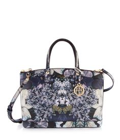 The West 57th Night Floral Satchel is an essential designer handbag for the girly girl on the go, featuring signature Henri Bendel hardware and plenty of pockets for your essentials. Crafted with Saffiano leather adorned with a custom floral print, this especially feminine luxury handbag includes a removable crossbody strap for versatile carrying.