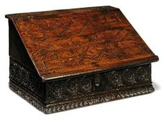 AN ELIZABETHAN OR JAMES I OAK SLOPE-LID DESK BOX  LATE 16TH EARLY 17TH CENTURY  The lid with geometrical inlay and centred with initials NW, the green-painted interior with lidded compartment and drawers, the front and sides carved with rosette-filled guilloche and gouge-carved rim 15 in. (38 cm.) high; 25½ in. (65 cm.) wide; 18 in. (46 cm.) deep