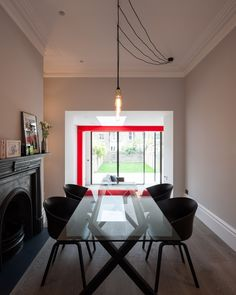 Tigg Coll Architects took a new approach to a straightforward town house renovation and expansion in London. The home's rear extension has its own personality, with with pivoting glass doors, sharp red support beams, and a wood-burning fireplace. Interior Architecture, Interior Design, House Extensions, Kitchen Extensions, Steel Beams, House Inside, Traditional Interior, One Bedroom Apartment, Beautiful Interiors