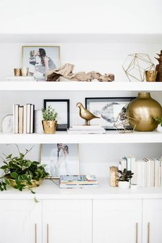White shelving styled with gold sculpture and books