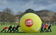 Onlookers were stunned as the country's largest tennis ball, the size of 140,000 standard balls, was rolled for a mile through Edinburgh. The 30kg, 13ft-wide ball appeared in front of various landmarks before rolling through the city's Meadows in aid of Sport Relief. The fluorescent ball was made by health and sport group David Lloyd Leisure, who are the Official Fitness Partner for Sport Relief 2014.