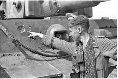A Tiger 1 crew member shows the minor damage on his tank after surviving a contact with Russian forces.