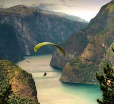 Paragliding along the Aurlandfjords    A fjord is a long, narrow bay with steep sides, created in a glacially carved valley that is filled by rising sea water levels. The seeds of a fjord are laid when a glacier cuts a U-shaped valley through abrasion of the surrounding bedrock by the sediment it carries. Many such valleys were formed during recent ice age when the sea was at a much lower level than it is today. At the end of the ice age, the climate warmed up again and glaciers retreated.