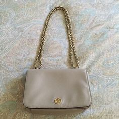 """Tory Burch Robinson Adjustable Shoulder Bag In excellent condition. Only used a few times. Leather has light creases. Color is Dust Storm Gray. Bought at Nordies. Can be worn as a shoulder bag or cross body.  DETAILS & FIT Leather. Flap with magnetic snap closure. Interior zipper pocket and open pocket. Exterior slide pocket at back. Leather and chain shoulder strap. Can be worn as a cross-body or a short shoulder bag. Height: 5.25"""" (13 cm) Length: 9"""" (22 cm) Depth: 3.5"""" (8 cm) Tory Burch…"""