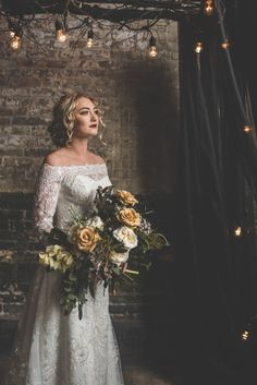 Deep Love – Moody Styled Photo Shoot - Bride with yellow and white rose wedding bouquet under canopy of lights and branches. #weddingbouquet