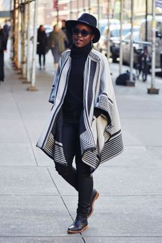 50 turtleneck outfit ideas for fall and winter from the best celebrity and street style looks: Lupita N'yono has the perfect cozy fall outfit in a black turtleneck, cape sweater and oversized hat