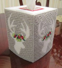 This is a pretty tissue topper perfect for the holidays. Each side has a reindeer adorned with poinsettias. Stitched on 10 count plastic canvas. Background is sparkly silver yarn for some extra bling