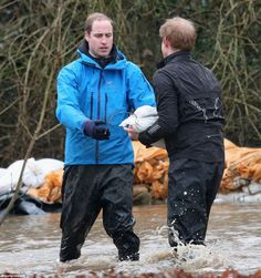 Teamwork: Princes William and Harry were knee deep in flood water at one point