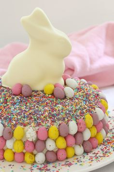 15 minutes is all it takes to whip up this show stopping Easy White Chocolate Easter Cake. It looks AMAZING but is the simplest recipe ever!!! A store-bought white chocolate mud cake covered in white chocolate frosting, heaped with pretty sprinkles and decorated with pastel chocolate Easter eggs and a white chocolate bunny… this really is the ultimate Easter cake! #easter #chocolate #easy #15minutes #cake #minieggs #eastereggs #bunny #video #recipe