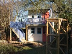 This childrens playhouse has an external staircase, allowing access to separate rooms on separate floors. A playhouse with two rooms: one downstairs and one upstairs, with separate access points allowing for separate play areas.The upper level is accessed via an external staircase to a balcony area protected by balustrade rails. The upper playhouse has two rectangular windows on the left hand side, two more rectangular windows and a door with heart shape cut on the front. Internally the…