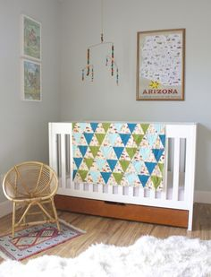 """""""A few months before I was due, I made Truman's quilt to hang on the side of his crib. The pattern on it is little cowboys, Native Americans, buffalo, and tee pees. I love that it became the base for the design of his room. I ordered the Arizona travel poster, found the vintage paint-by-numbers of colts at an antique shop, and made the mobile out of copper wire and puffs."""""""