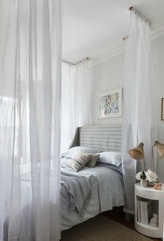 Fake a four-poster bed with ceiling-mounted curtain hardware