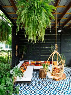 The enclosed patio area is also packed with colour and personality. From the oversized ferns that cascade above the space and bring a touch of greenery to this area, to the beautiful choice of patterned flooring. Colourful scatters hint at the colourful array of furnishings used in the interior – enhancing the indoor-outdoor living feel of this home.