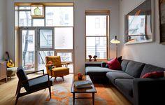 A geometria de portas e janelas somada à combinação de preto e laranja estabelece a identidade do living deste apartamento no Harlem, em Nova York.