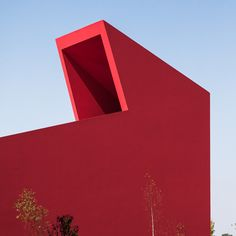 Bright red walls contrast with vivid green lawns at this art and culture centre #Architecture