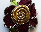 floral brooch which measures approximately 1.75 inches, 4.5 cm. It is backed with felt and has a nickel pin back.
