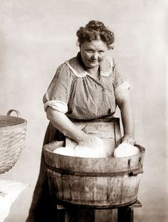 picture was taken in 1900, and shows a woman doing the wash in a wash tub with a scrub board