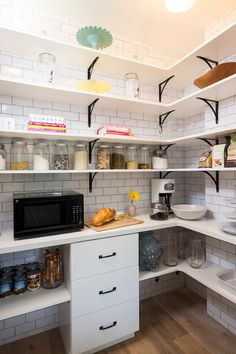 U shaped walk-in pantry features stacked shelves accented with black iron corbels on ceiling height subway tiled wall